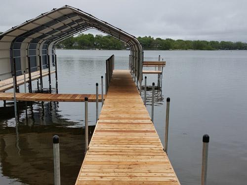 cedar dock below striped boathouse on Lake Minnetonka